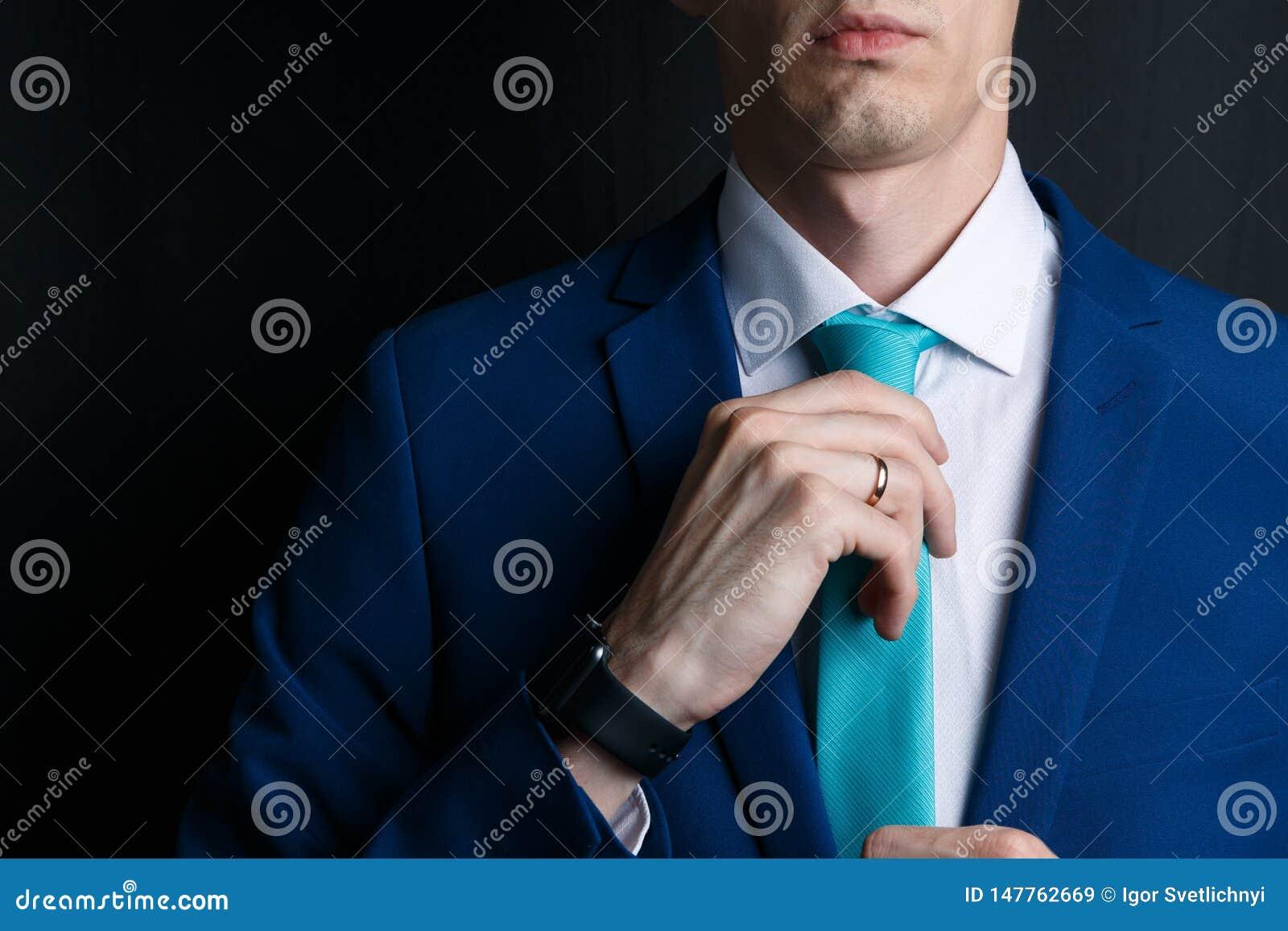 W g?r? m?odego cz?owieka w kostiumu Jest w bia?ej koszula z krawatem M??czyzna prostuje jego krawat