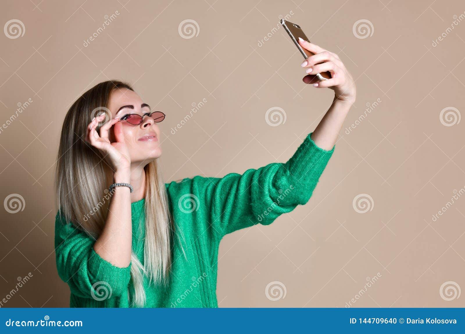 W g?r? portreta m?oda rozochocona mody blondynki kobieta w pulowerze odzie? robi selfie na smartphone, nad be?owym t?em