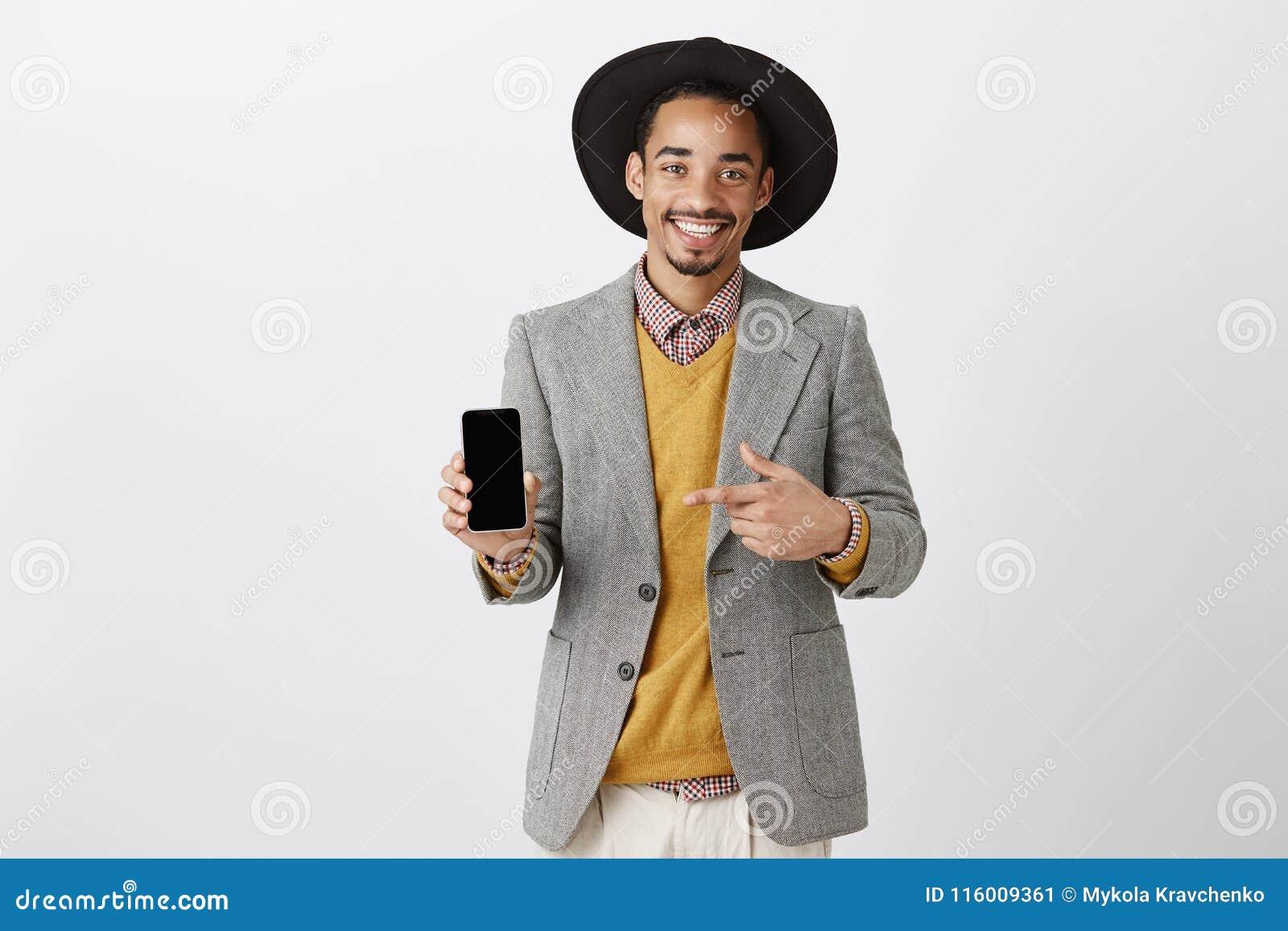 W końcu nowy model smartphone Pozytywny szczęśliwy facet w eleganckim stroju i kapeluszu pokazuje smartphone i wskazuje przy przy