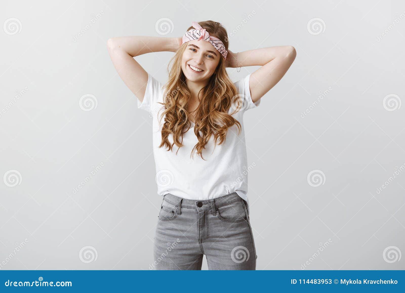 W końcu wydawać czas dla ja może Zrelaksowany atrakcyjny żeński uczeń w modnej kapitałce i przypadkowej koszulce trzyma,