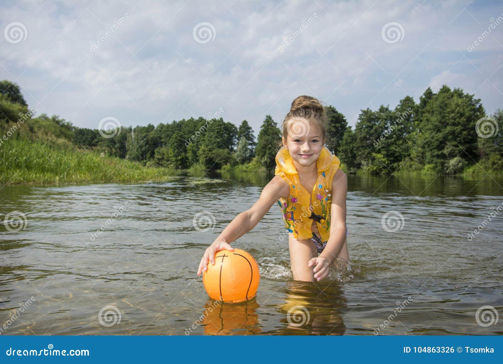 W lecie, na rzece, dziewczyna w kamizelce bawić się z piłką