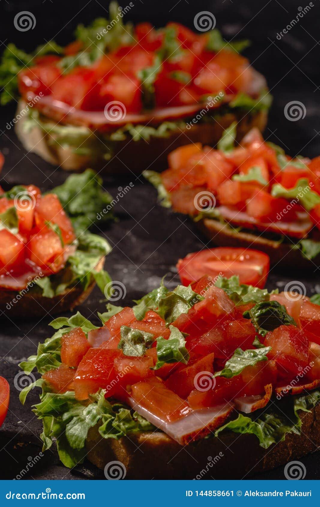 W?oski pomidorowy bruschetta z warzywami, ziele i olejem na skorupiastym ciabatta chlebie siekaj?cymi, piec na grillu lub wznosz?
