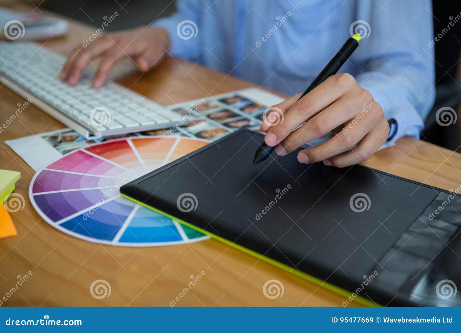 W połowie sekcja żeński projektant grafik komputerowych używa grafiki pastylkę przy biurkiem