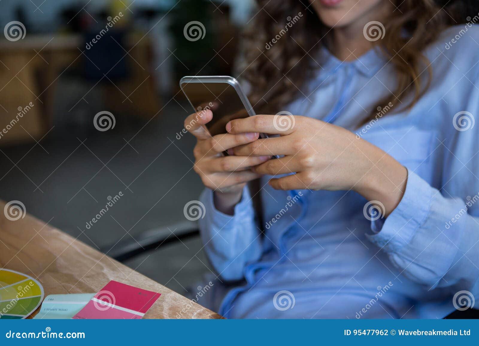 W połowie sekcja żeński projektant grafik komputerowych używa telefon komórkowego