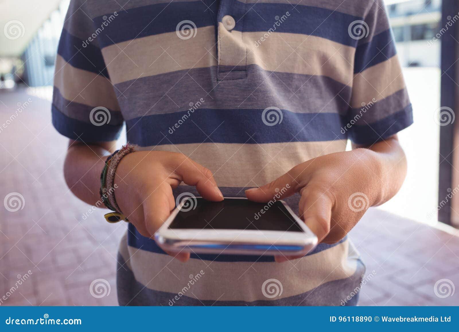 W połowie sekcja chłopiec używa telefon komórkowego