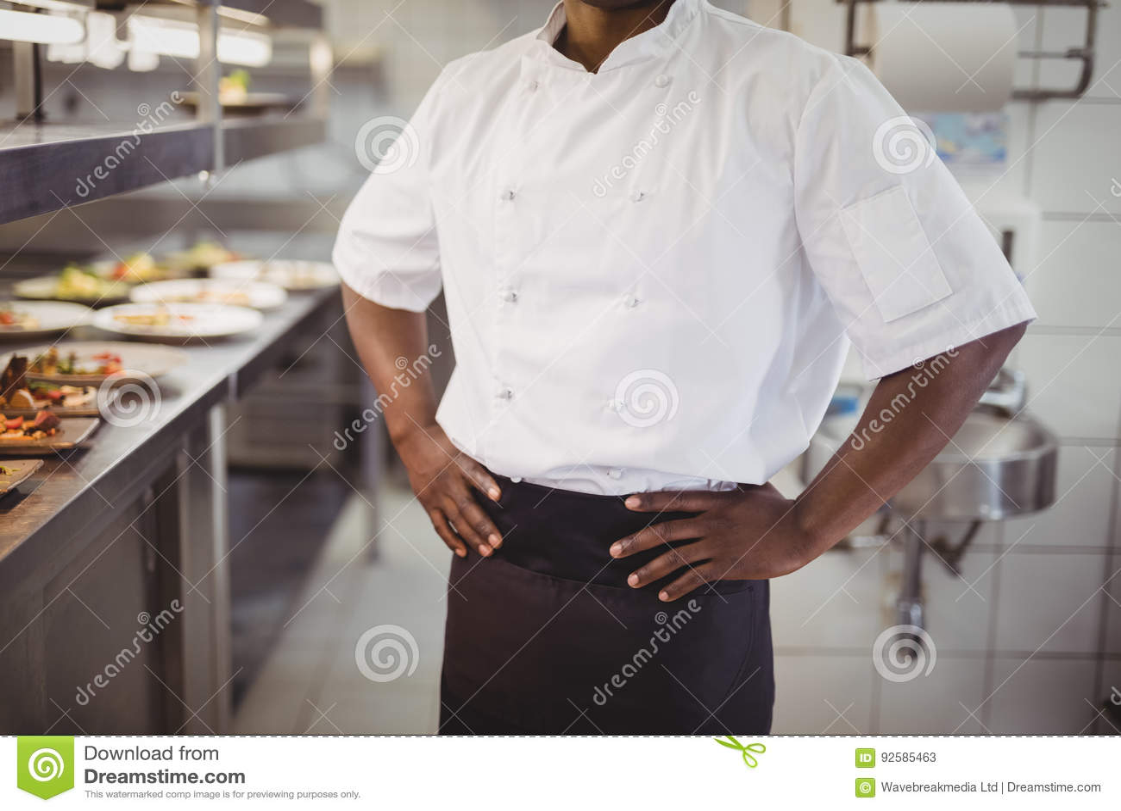 W połowie sekcja szef kuchni pozycja z rękami na biodrze w handlowej kuchni