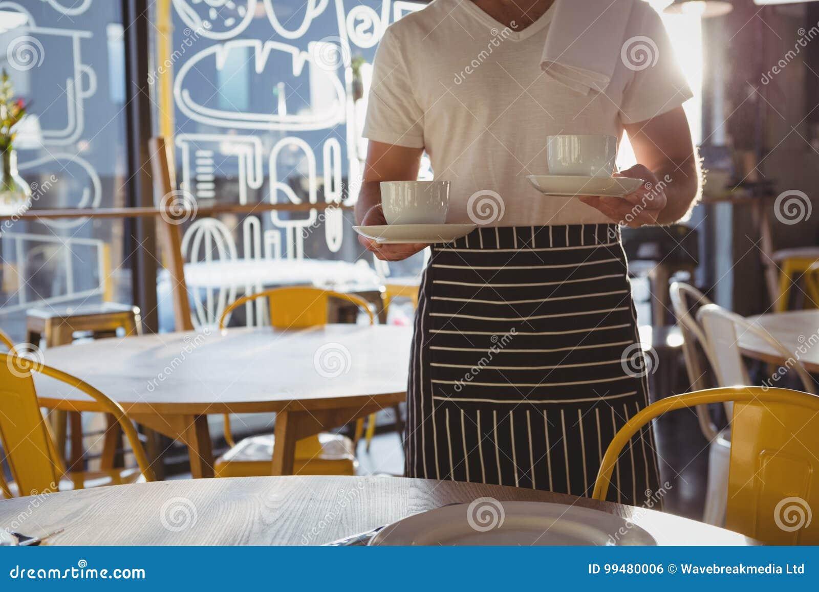W połowie sekcja trzyma filiżanki kelner