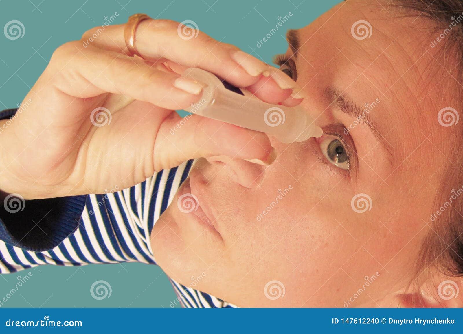 W ?rednim wieku kobieta opuszcza oczy Makro- zbli?enie wizerunek twarz Medyczna procedura w domu Dziewczyny mienia eyedropper zrz