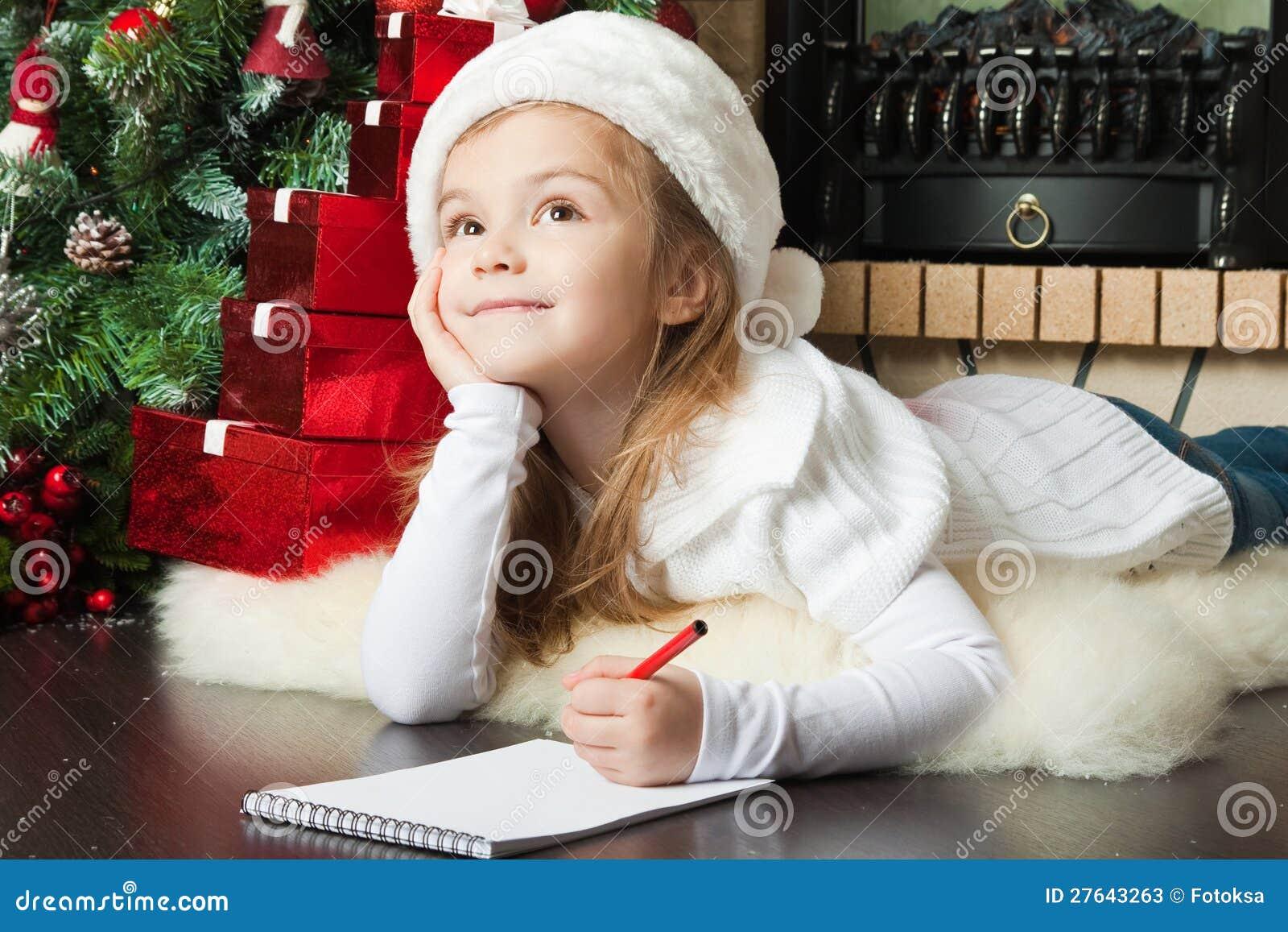 W Santa kapeluszu ładna dziewczyna pisze liście Santa