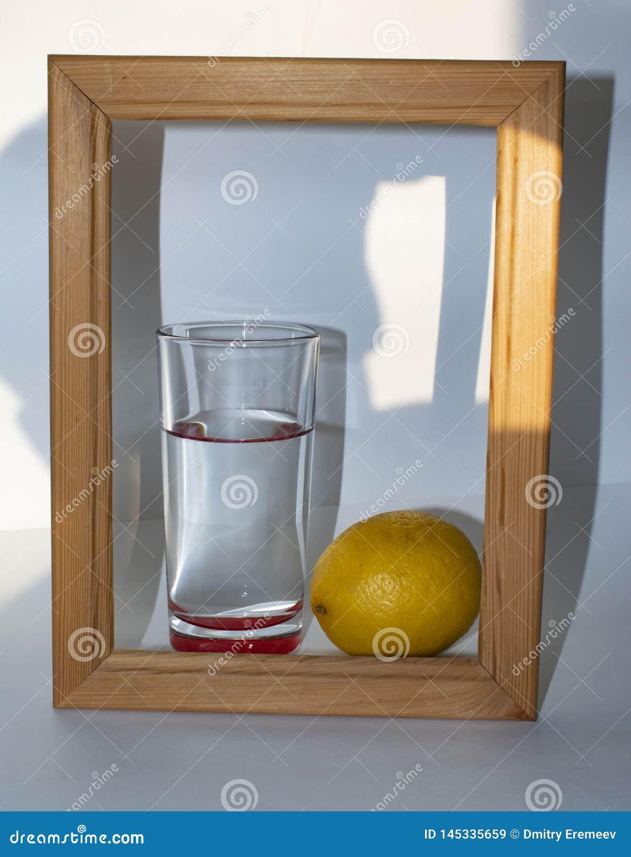 W szkle czysta jasna woda obok cytryny