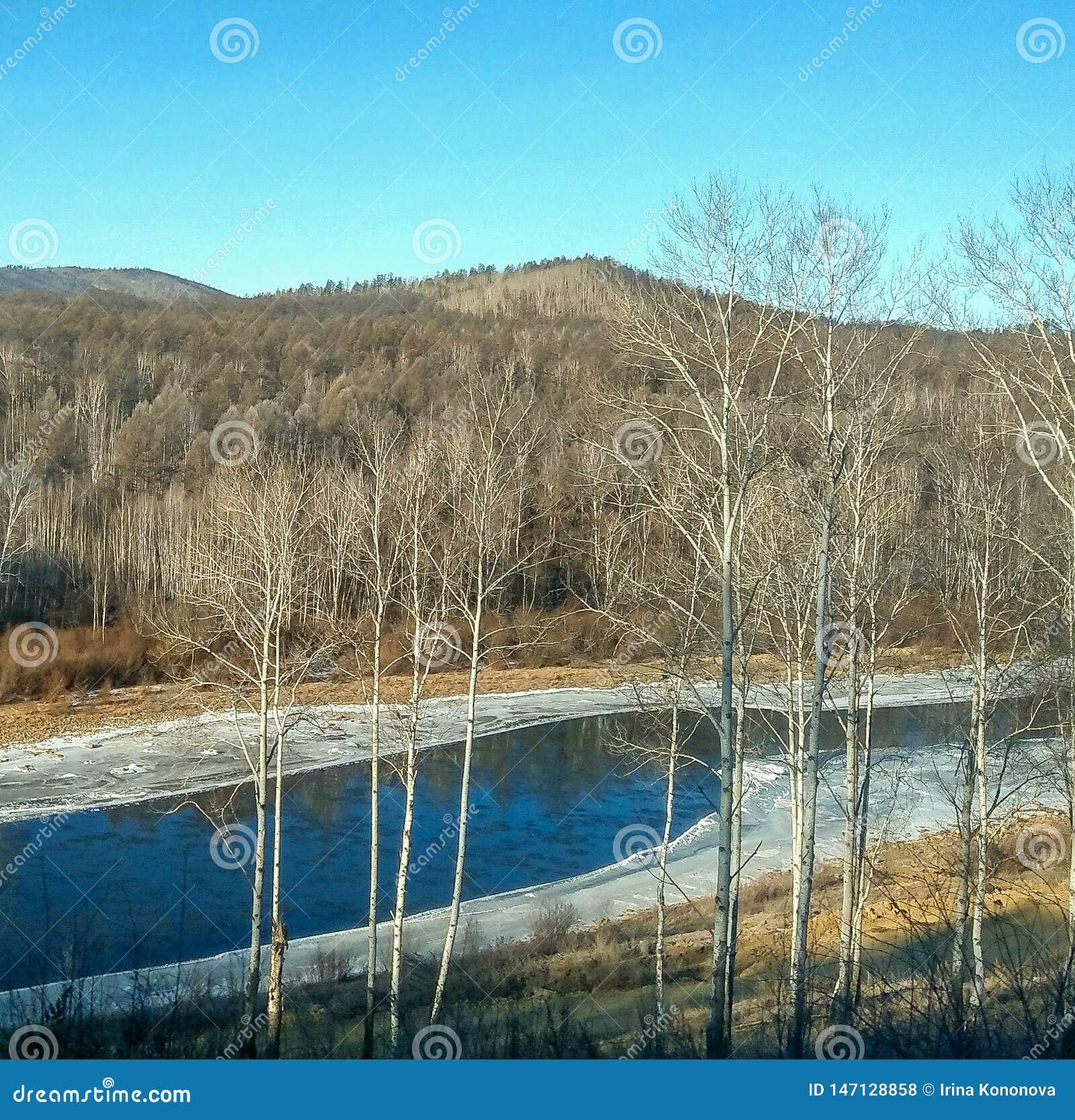 W zimie rzeka płynie wśród marznących banków i wzgórzy