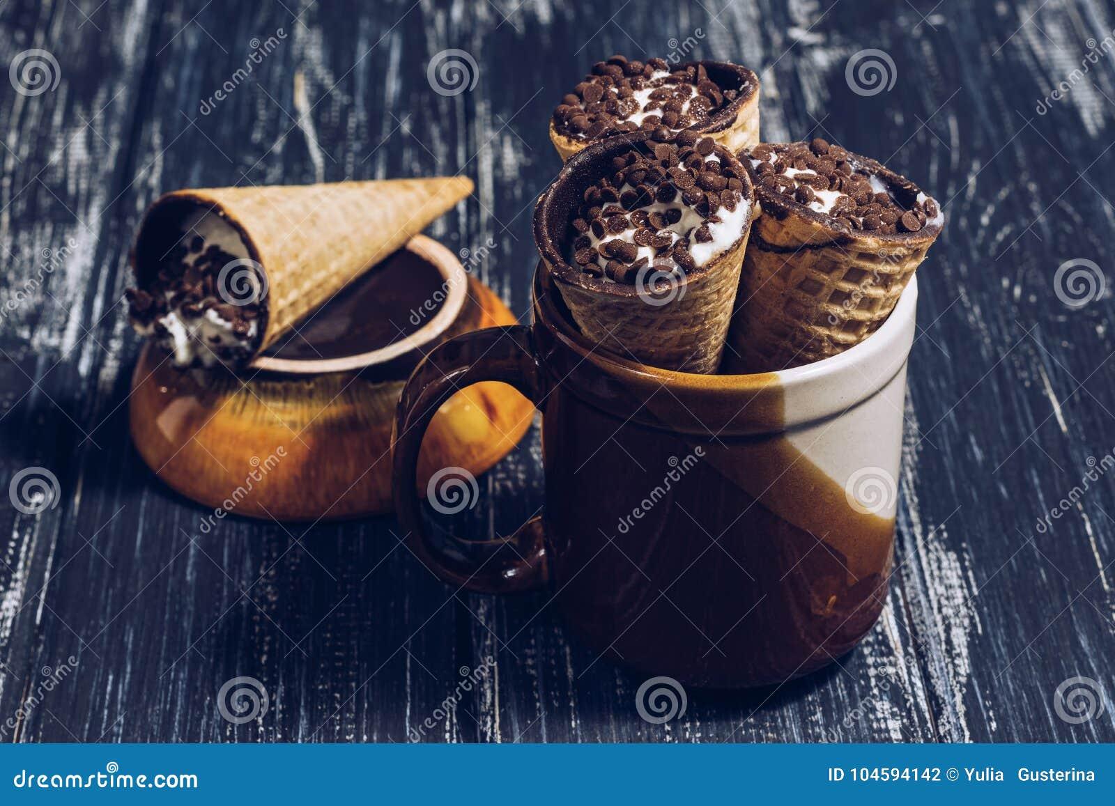 Wafelhoornen met room of kwark met chocolade wordt bestrooid die Dessertwafel