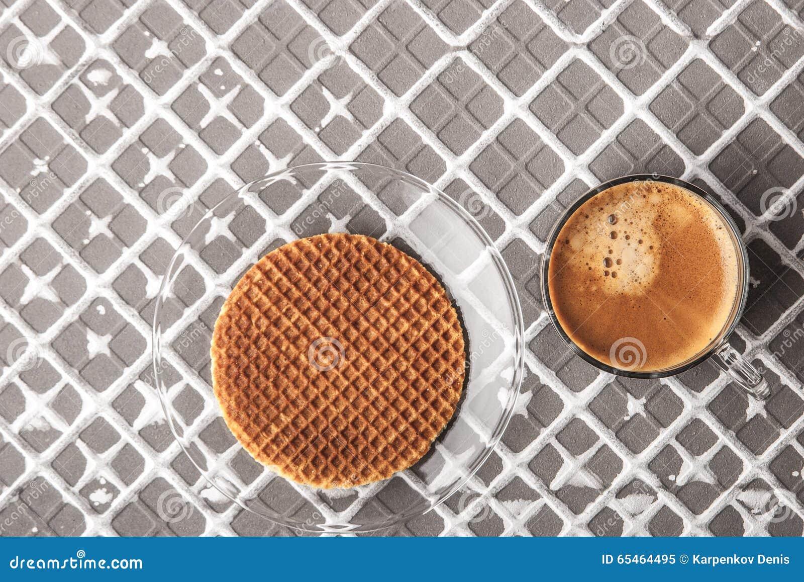 Wafeltje met kop van koffie op de horizontale hulpachtergrond