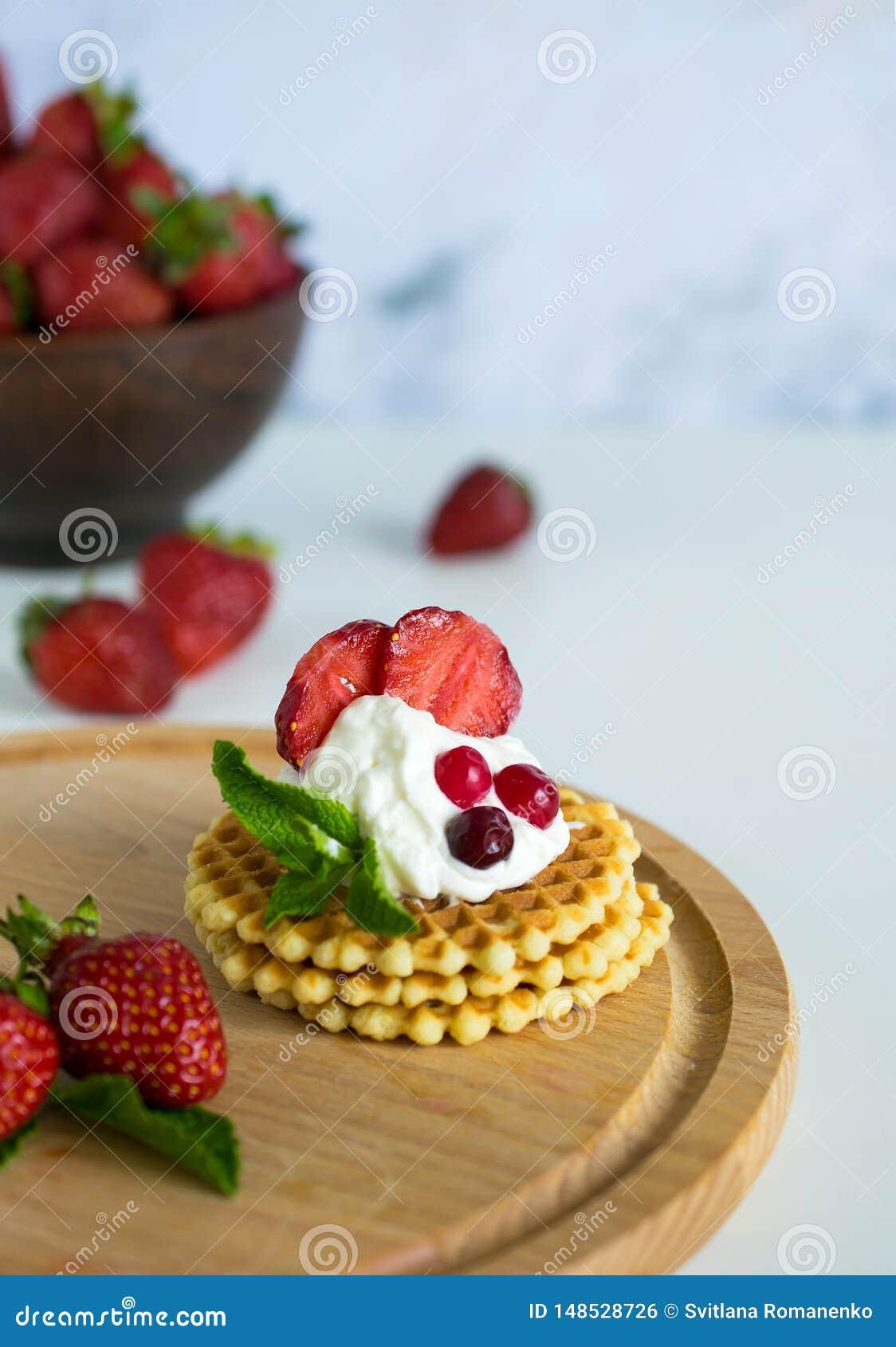 Waffles belgas deliciosos com creme e as morangos wipped
