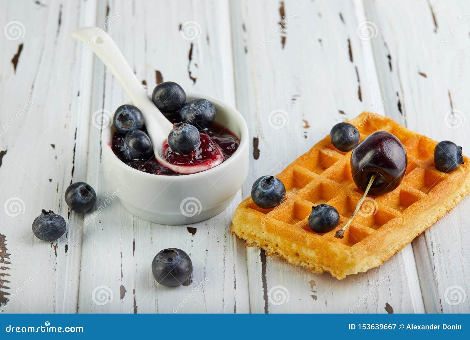 Waffles belgas do café da manhã saboroso com mirtilos e doce do chantiliy em um branco de madeira