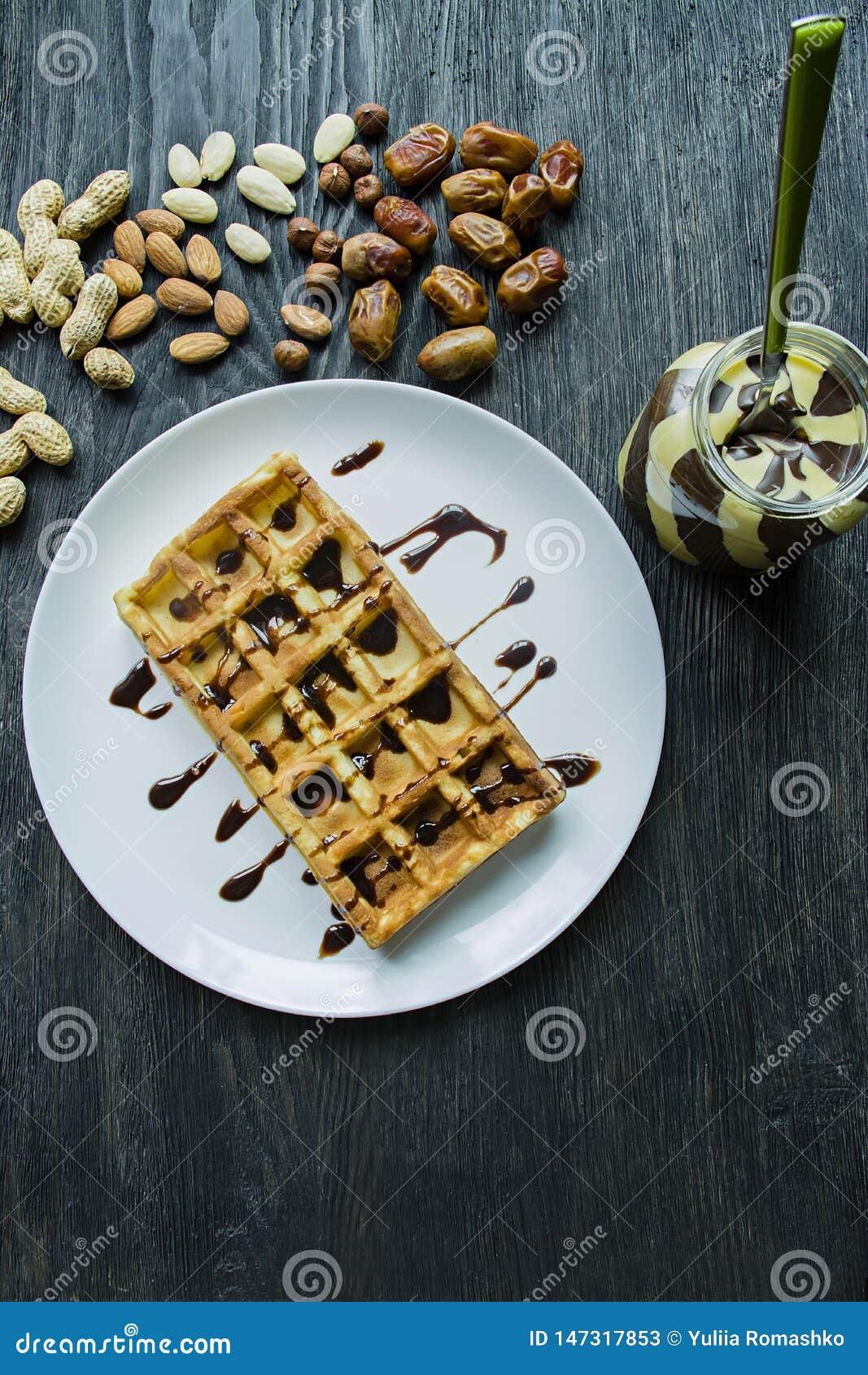 Waffles belgas tradicionais cobertos no chocolate em um fundo de madeira escuro Pequeno almo?o saboroso Decorado com porcas do ra
