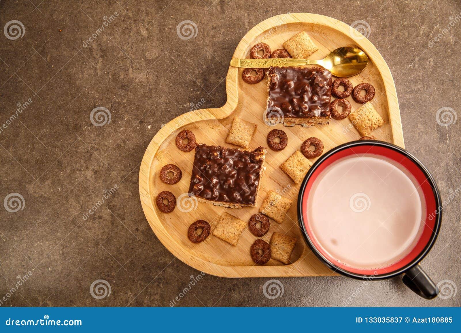Waffles e cookies do chocolate em uma bandeja de madeira na forma de um coração e de um copo do chocolate quente