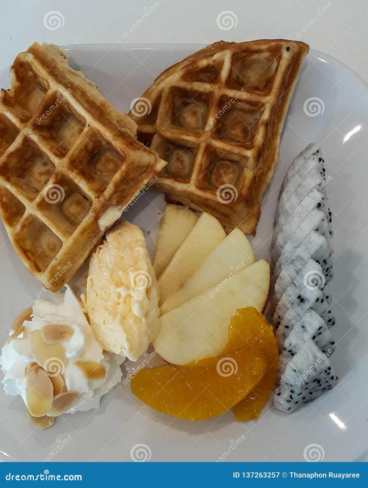 Waffles uma sobremesa doce como o petisco dentro do decorado belamente