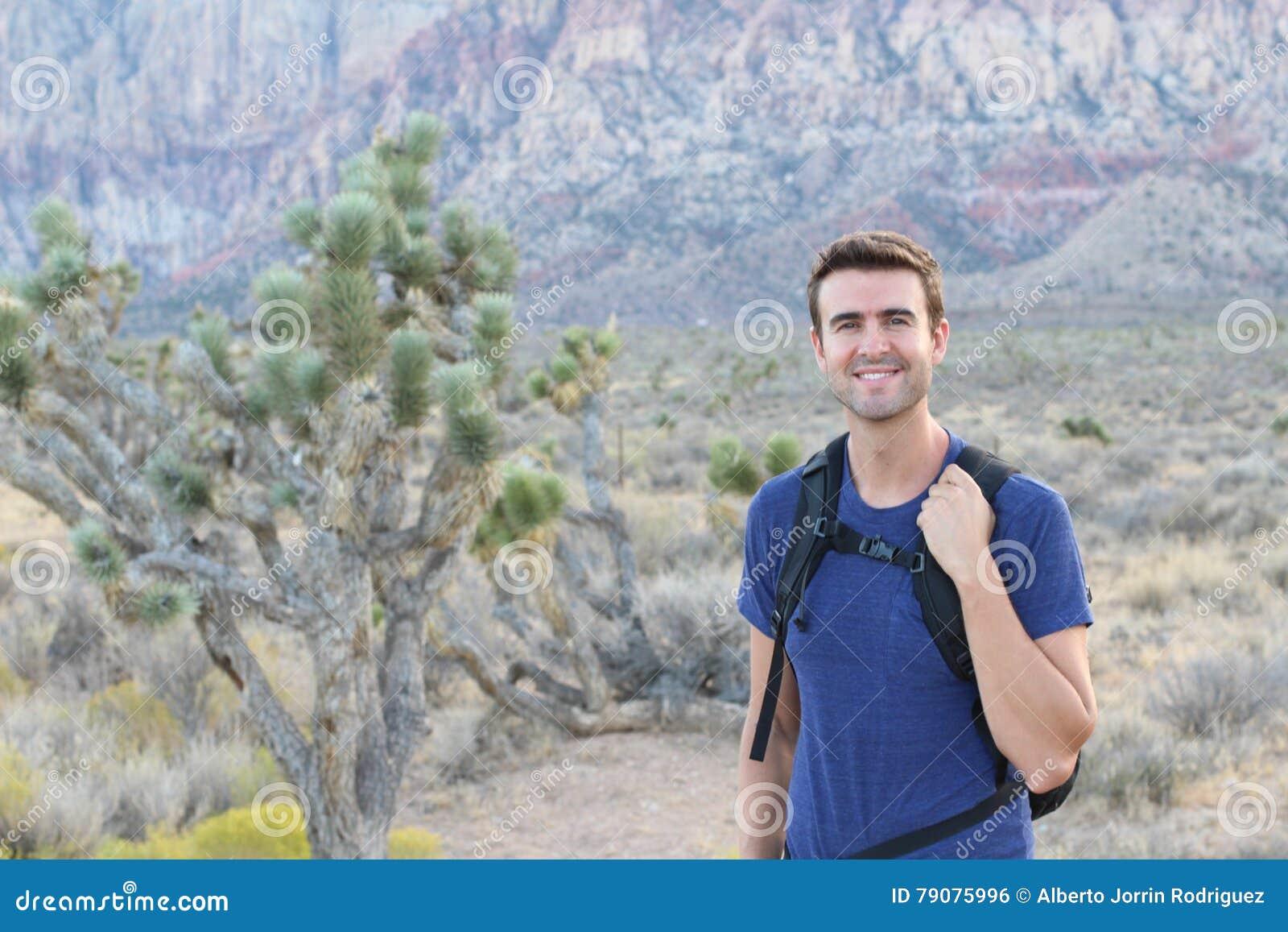Wagen Sie, reisen Sie, Tourismus, Wanderung und Leutekonzept - bemannen Sie den tragenden schwarzen Rucksack, der in den felsigen
