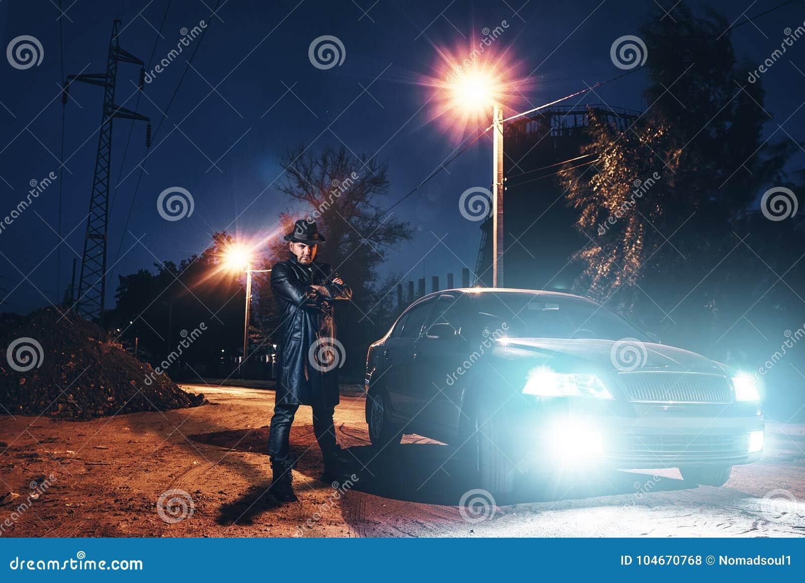 Wahnsinnige im Ledermantel und im Hut gegen schwarzes Auto