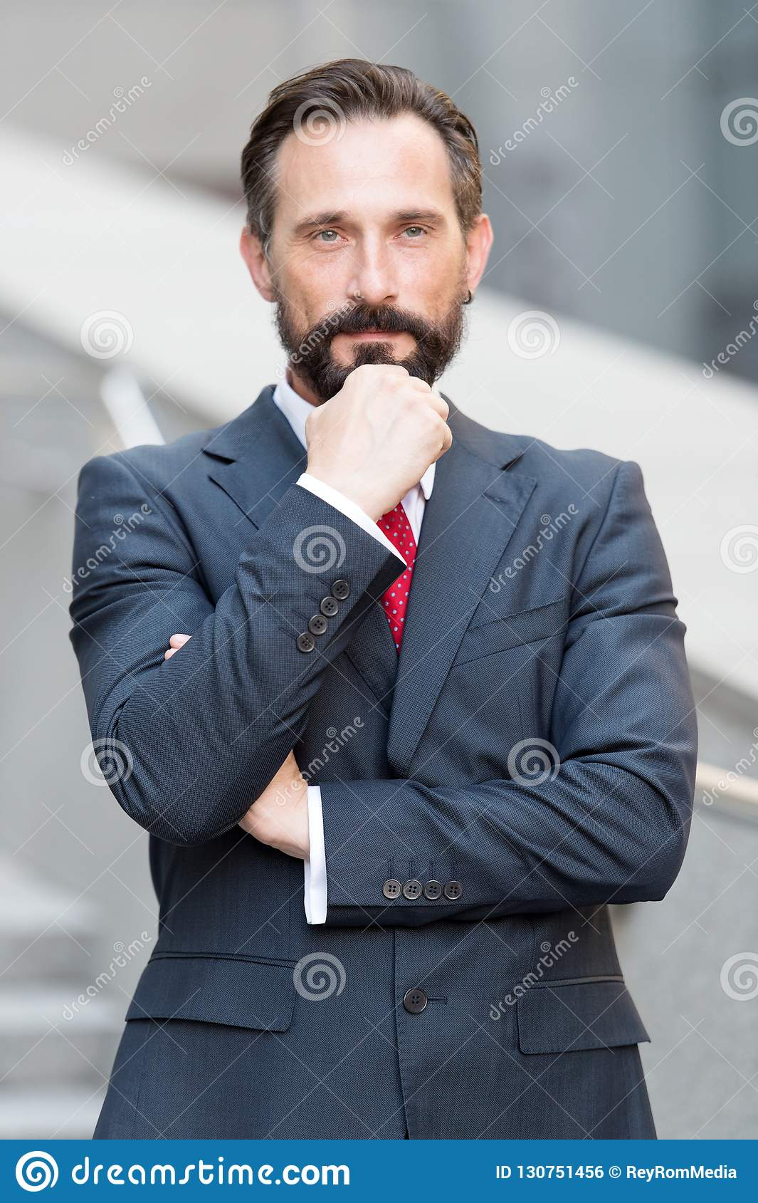 Waist up of calm man touching his beard and looking at you