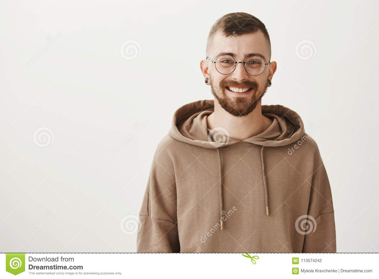Waist-up indoor shot of friendly handsome hipster guy with trendy haircut and glasses smiling cheerfully while standing