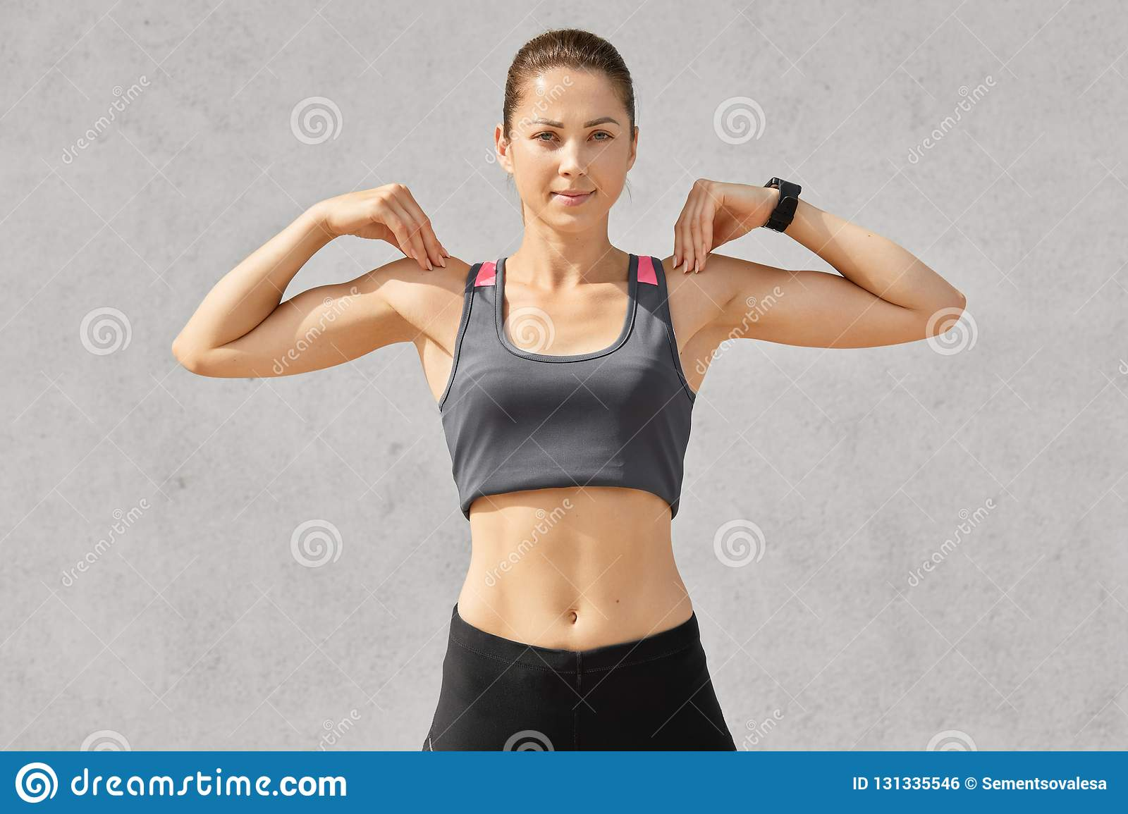 Waist Up Shot Of Sporty Woman Keeps Both Hands On Shoulders