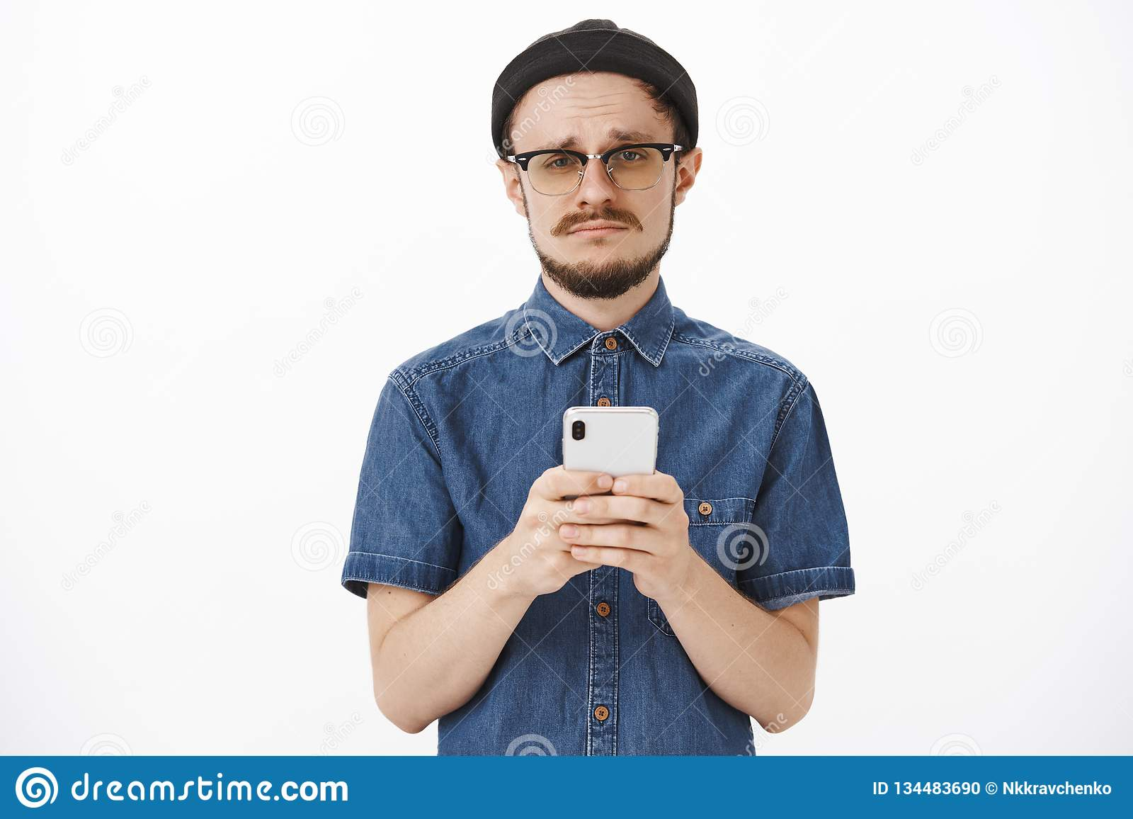 Waist-up shot of upset gloomy cute bearded guy in black beanie and glasses  making a54bebf8941