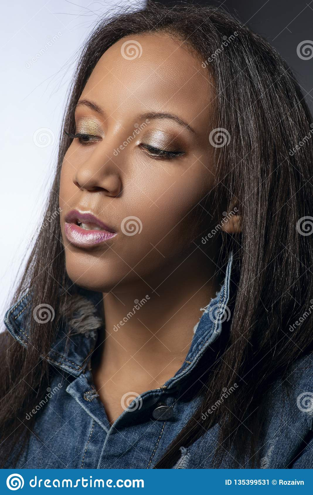 Waist up studio shot of the attractive woman of the mulatta with make up wearing jeans dress