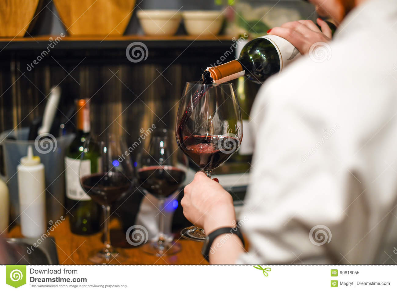 Waiter pouring wine. Skillful sommelier pouring red wine into glass. Woman holding bottle and wineglass standing in