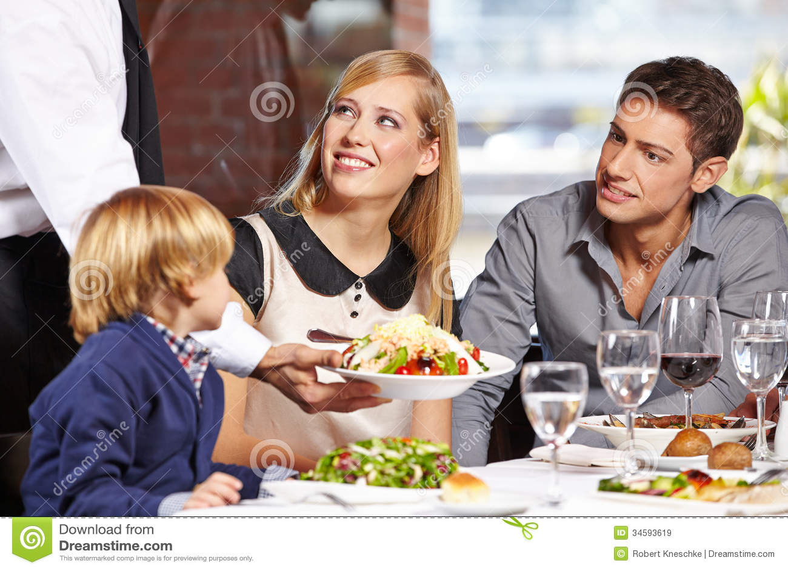 Waiter serving family in restaurant