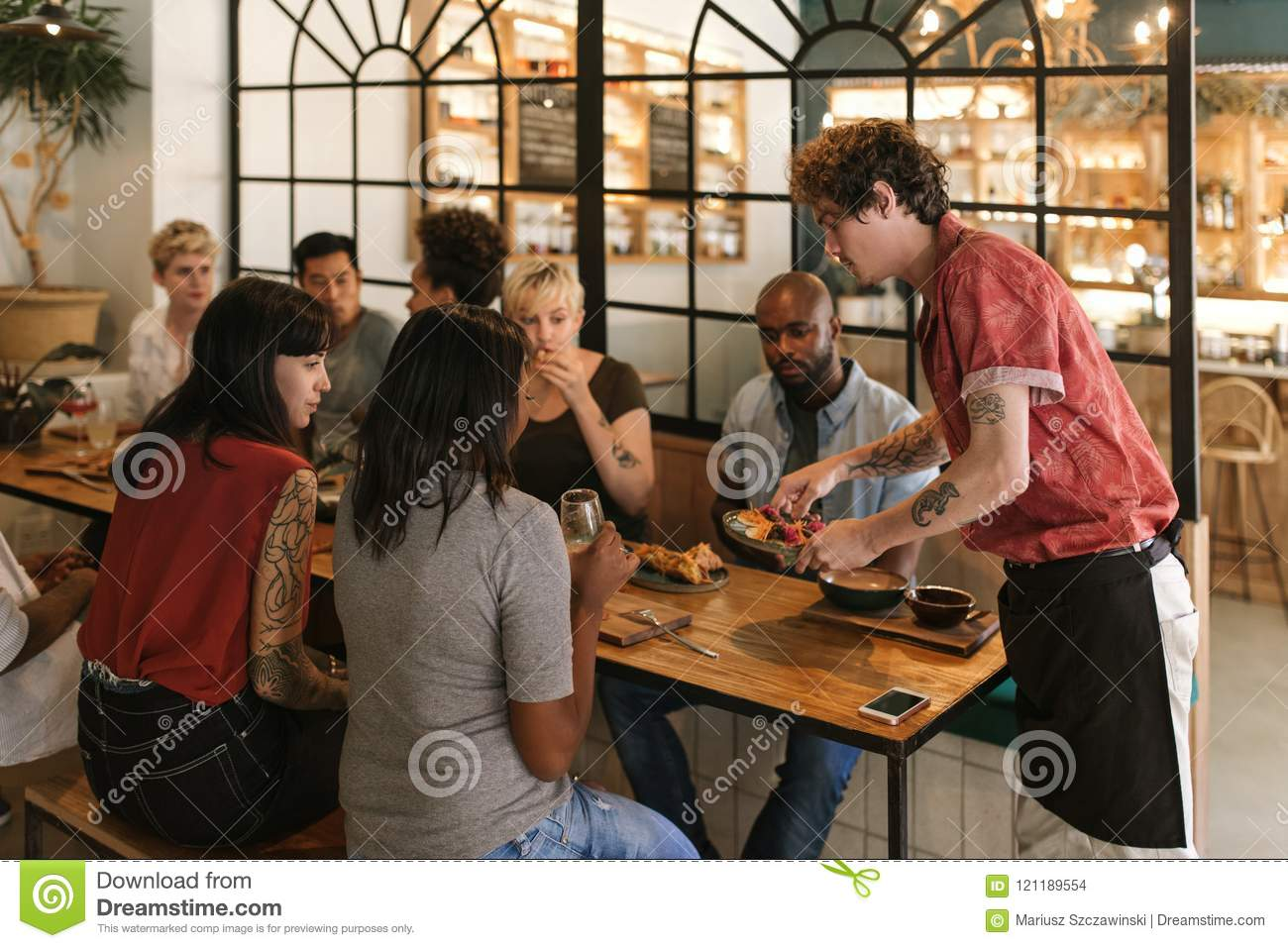 Waiter serving freshly made food to smiling bistro customers