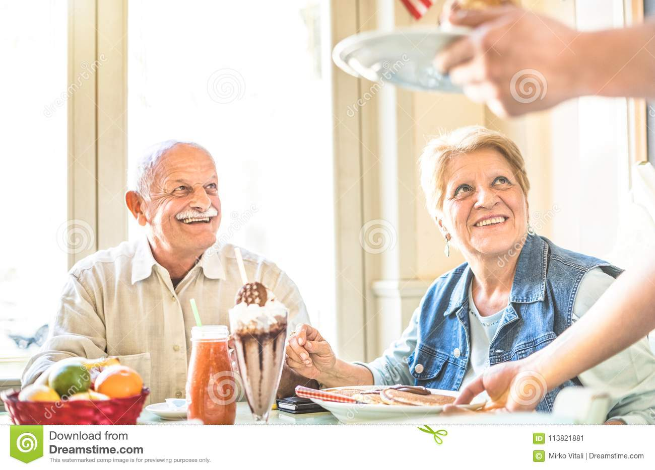 Waiter serving senior retired couple eating cakes at fashion bar