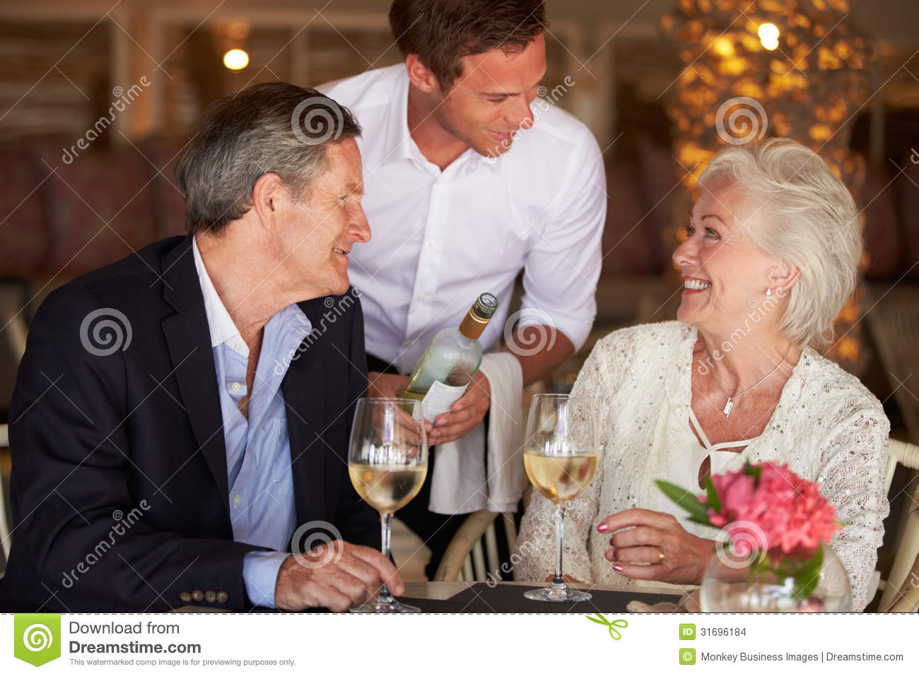 Download Waiter Serving Wine To Senior Couple In Restaurant Stock Photo - Image of retired, food: 31696184
