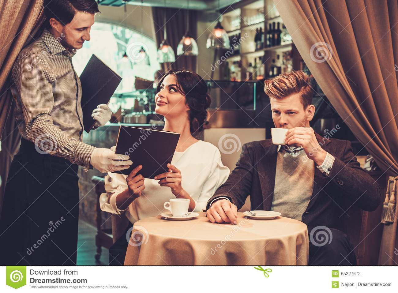 Waiter taking order from stylish wealthy couple