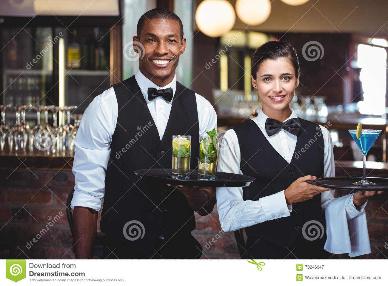 Waiter and waitress holding a serving tray with glass of cocktail