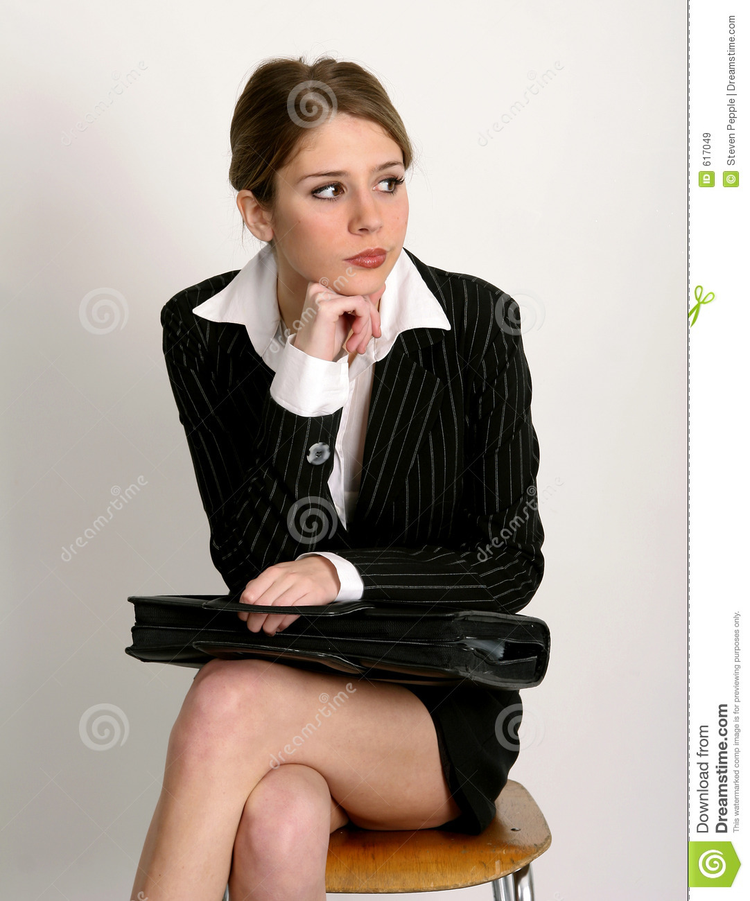 Young woman in business suit sitting on chair with briefcase in her