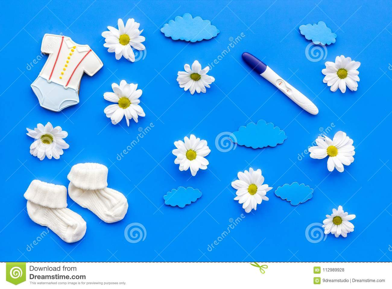 Waiting for a baby with positive pregnancy test and flowers blue background top view