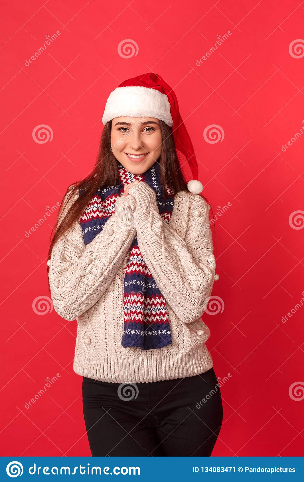 Waiting for Celebration. Young woman in scarf and santa hat standing isolated on red hands together smiling happy