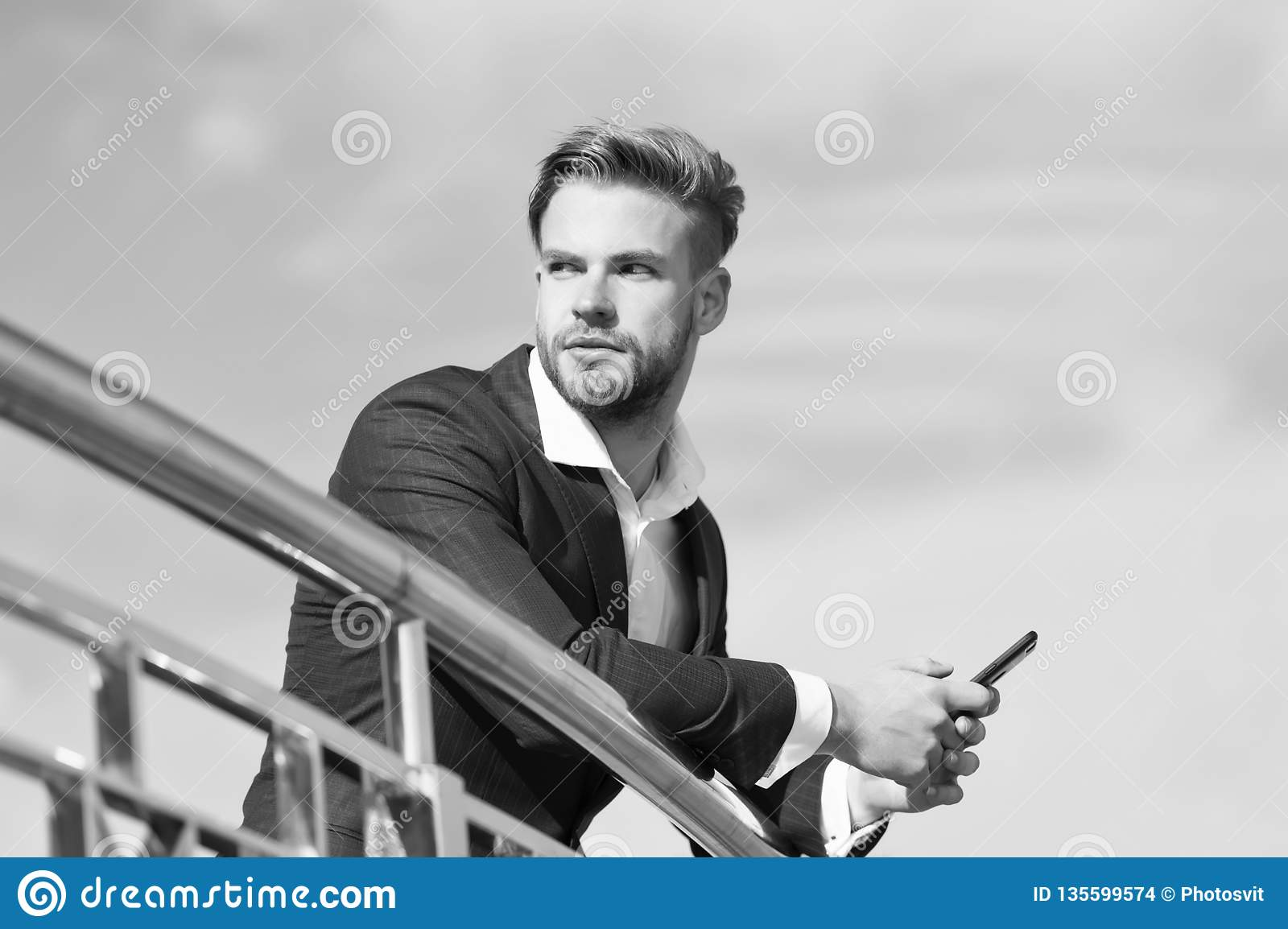 Waiting important call from partner. Businessman use smartphone for video call or texting sky background. Man in suit