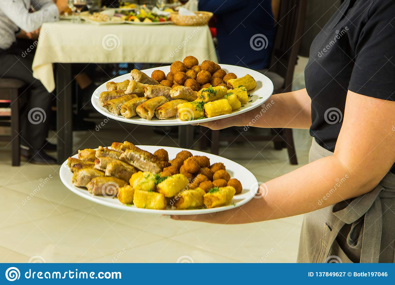 Waitress with food dish serving banquet table