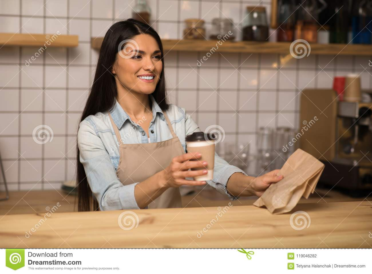 Waitress holding coffee to go and take away food in cafe