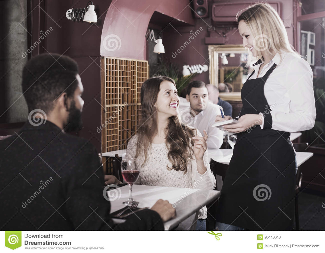 Waitress serving meal for young couple at table