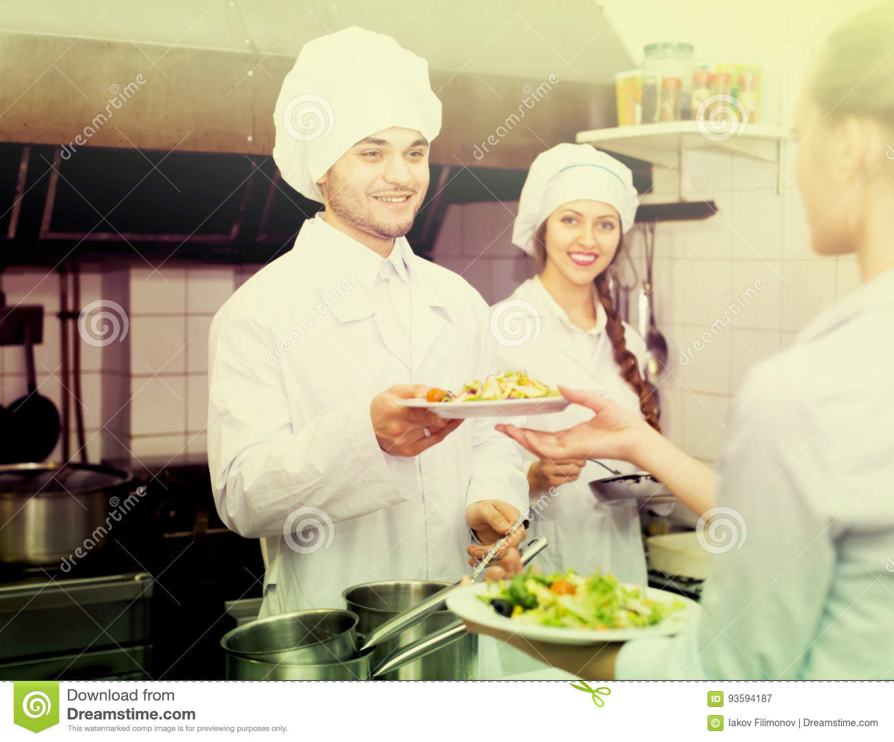 Waitress taking dish from kitchen