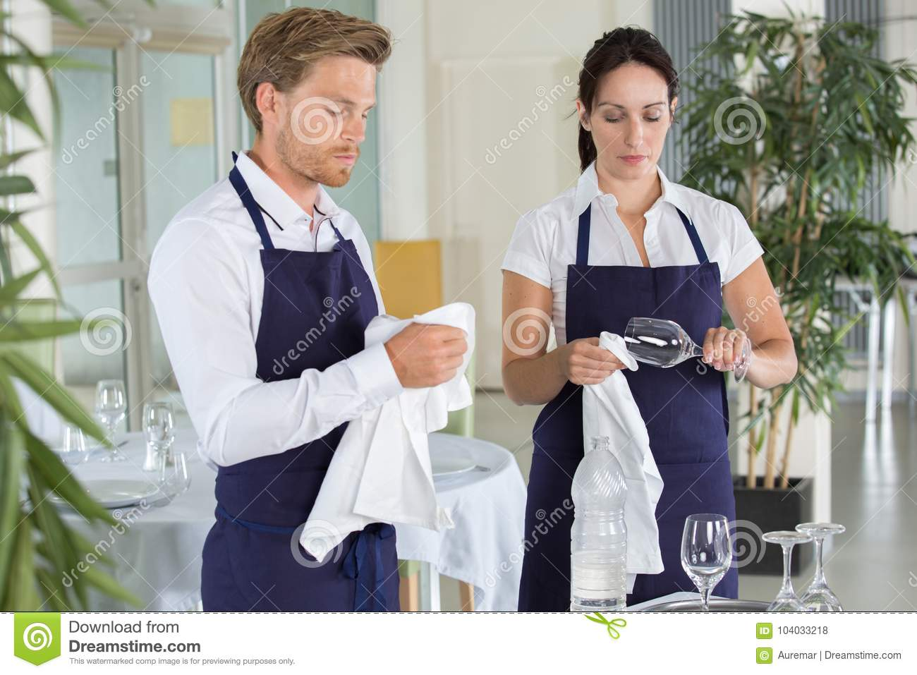 Waitress and waiter cleaning glasses in restaurant