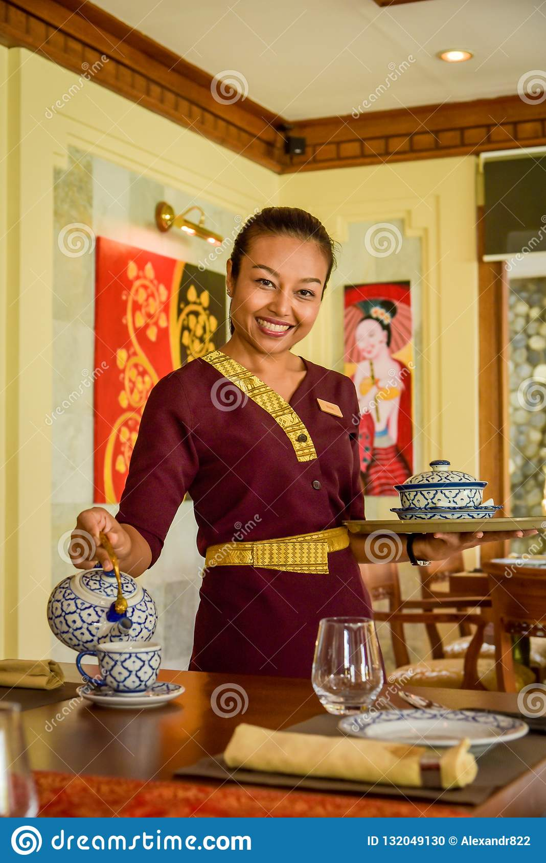 Waitress wearing uniform in the thai restaurant serving tea with a smile