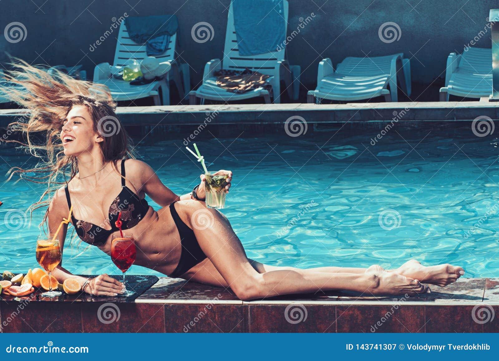 Wakacje i pływać przy morzem Basenu przyjęcie relaksuje w zdroju kurorcie Mody kobieta z odświeża alkohol w Miami
