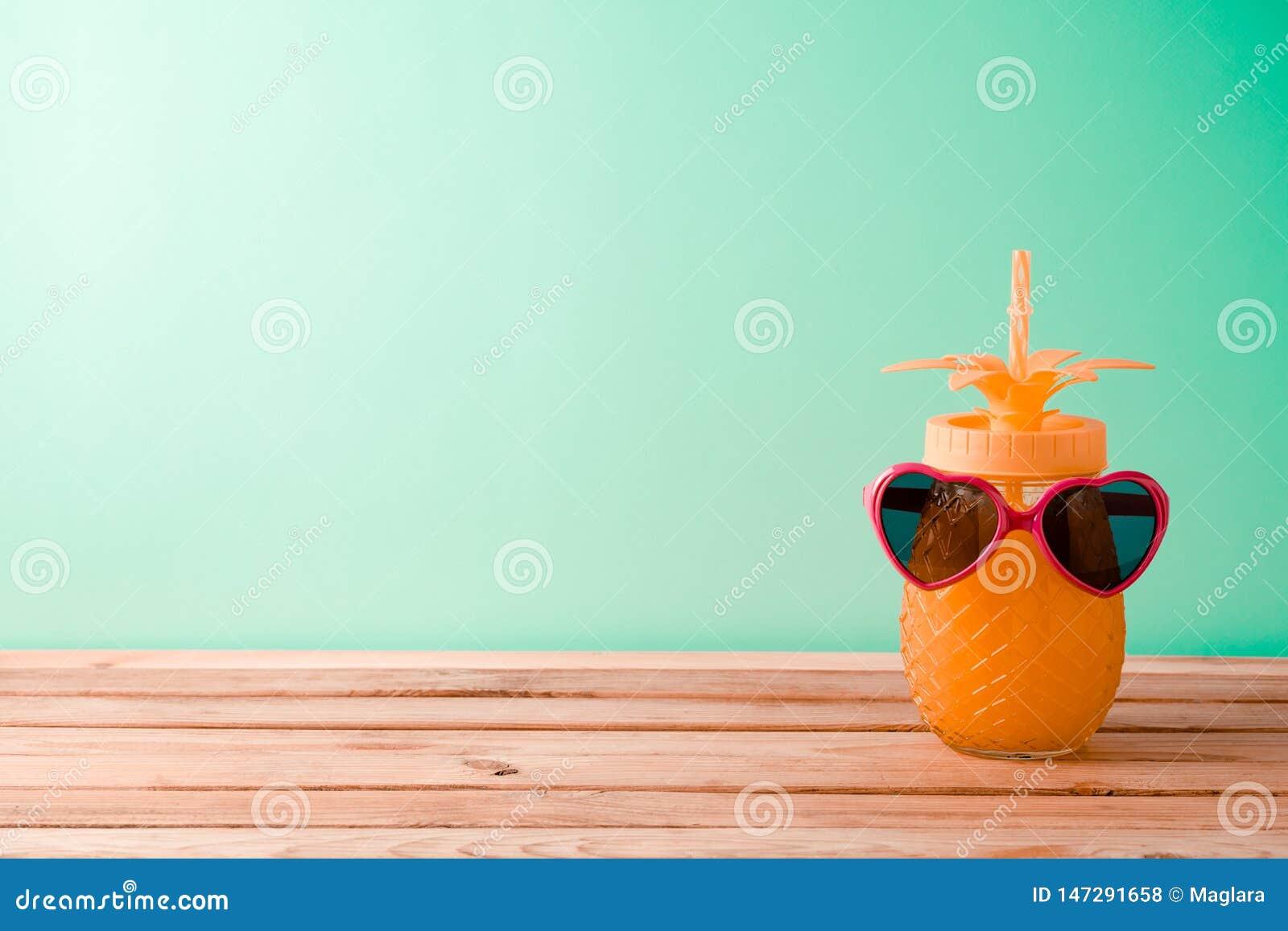 Wakacje tło z ślicznym ananasowym sokiem i okularami przeciwsłonecznymi na drewnianym stole