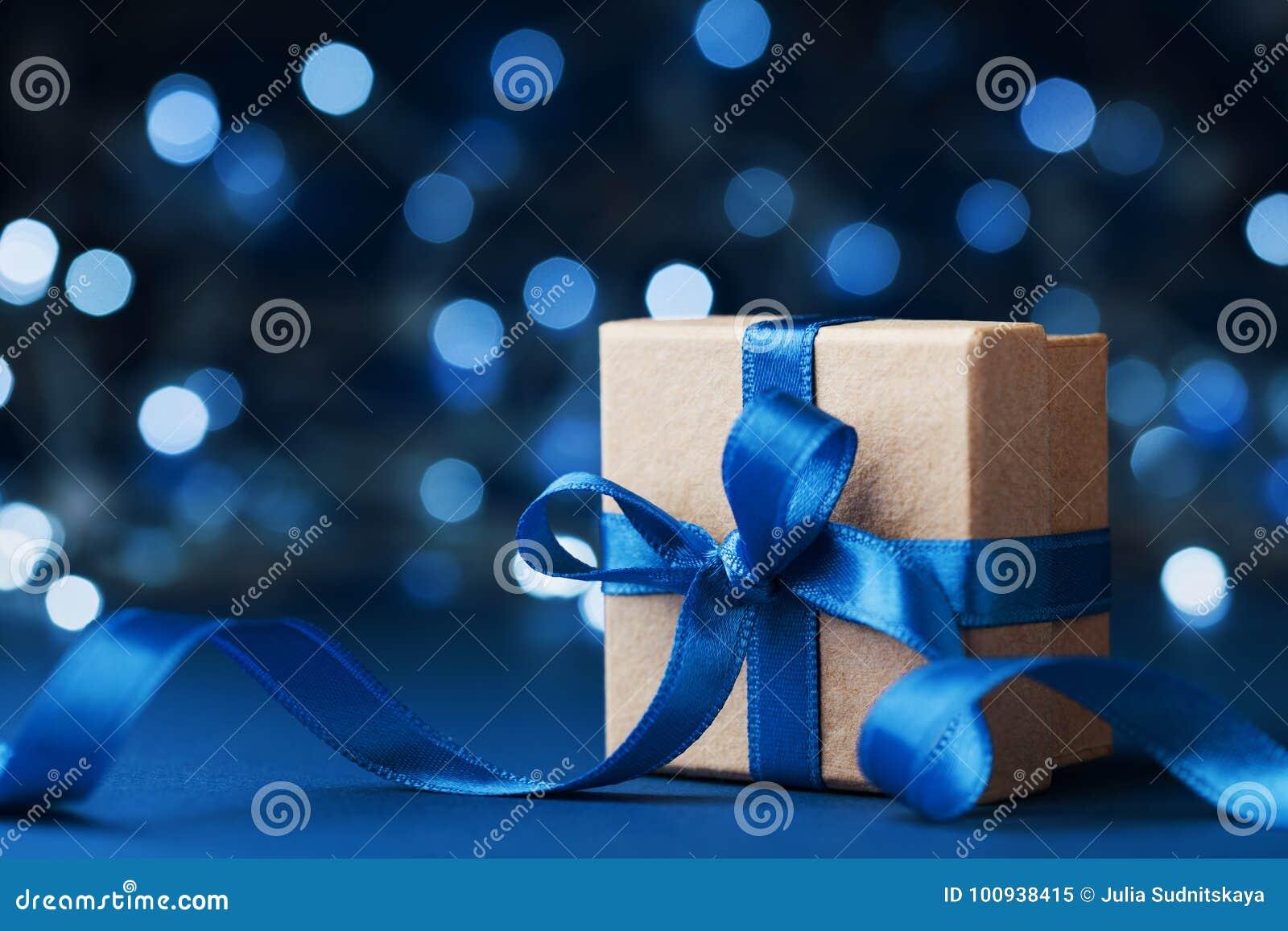 Wakacyjnego prezenta teraźniejszość z łęku faborkiem przeciw błękitnemu bokeh tłu lub pudełko Magiczny bożego narodzenia kartka z