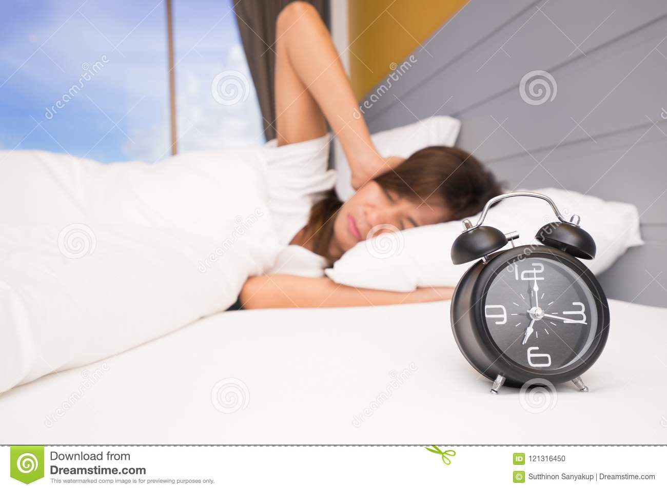 Wake up, Asian woman in bed extending hand to alarm clock. girl turns off the alarm clock waking up in the morning. Young sleeping